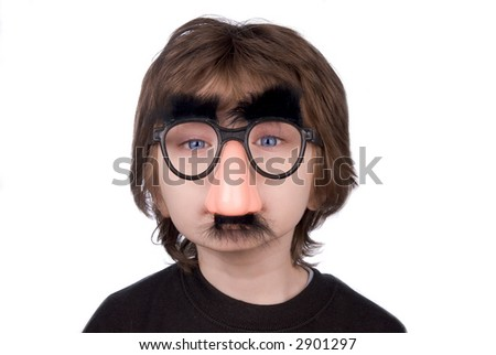 Boy wearing fake nose and glasses with mustashe and eyebrows over a white background