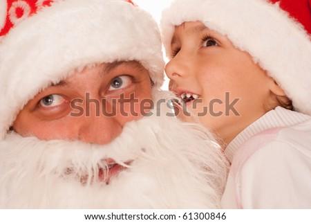 boy whispers to Santa on a white background