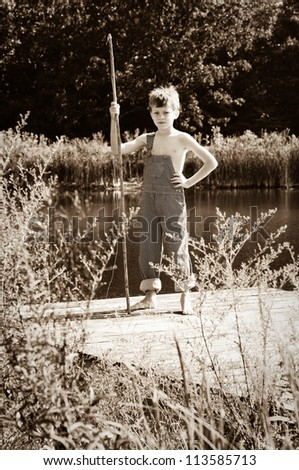 Boy with a fishing pole in overalls standing on a dock on lake or pond.