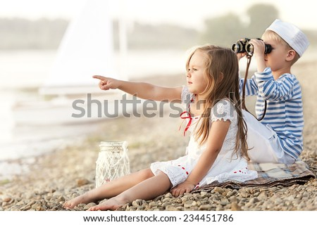 Boy with a girl sitting on the beach with binoculars and looking into the distance on a sunny summer afternoon lake
