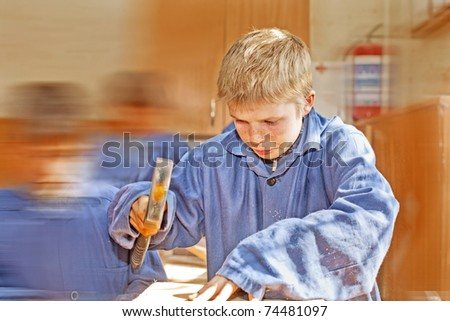 Boy with a hammer in overalls