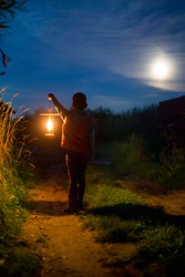 boy with a lantern. child with a lantern in his hand outdoors at night