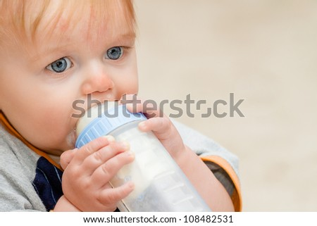 Boy with a milk bottle up to his mount drinking away while seated. There is some milk leakage around the mount and upper lip