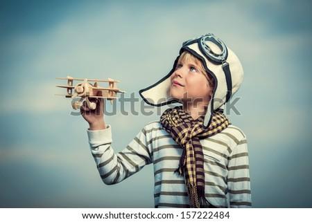 Boy with a plane on sky background