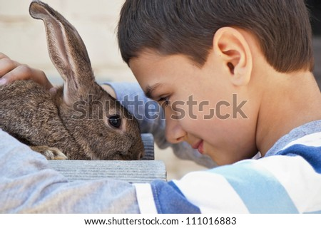 boy with a rabbit in the garden at the cottage