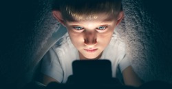 Boy with a serious face under the blanket at night in his bed communicates on Internet. Child gadget addiction and insomnia.