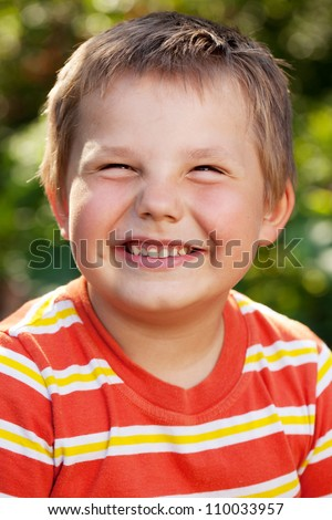 Boy with a smile on his face in an orange striped shirt