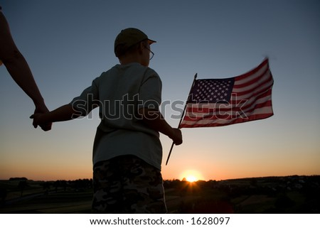 Boy with American flag and his parent at sunset.