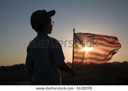 Boy with American flag at sunset.