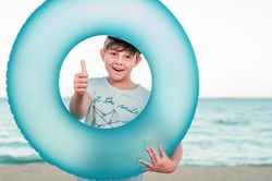 Boy with an inflatable swimming ring on the seashore. Portrait of a boy in the center of a blue swimming circle on the beach. Child dreams of sea travel. Boy shows sign like, thumb up. Travel dreams