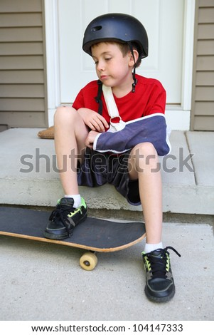 Boy with arm in a sling sits on a porch wishing he could skateboard again