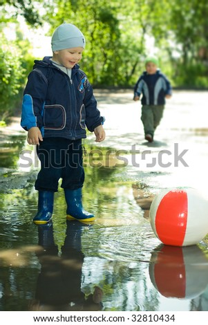 boy with ball in the puddle