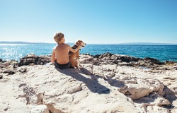 Boy with beagle dog sitting together on rocky sea coast at sunny afternoon