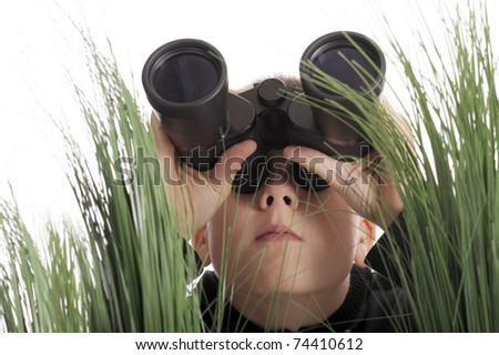 boy with binoculars lying in grass