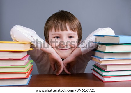 Boy with books on a gray background