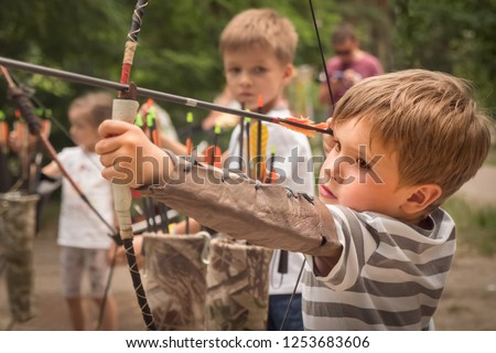Boy with bow and arrow concentrated on target. Kid stared at target. Child directed arrow at a target. Bowman background. Children and sports. Physical training. Alternative schooling.