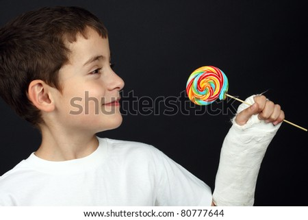 Boy with broken hand in cast, holding a lollipop