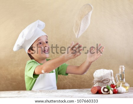 Boy with chef hat preparing the pizza dough - kneading and stretching - stock photo