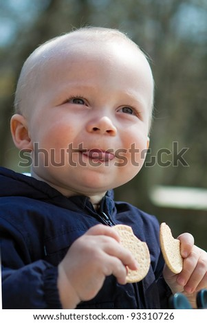 Boy with cookies puts out the tongue