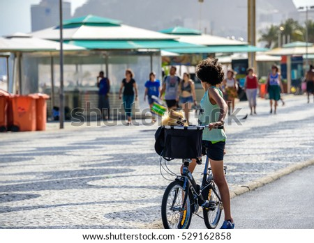 Boy with curly hair with his head turned back standing with bicycle and with dog in a basket on the bike path of Copacabana beach with the background of blurry walking people, Rio de Janeiro, Brazil Foto stock ©