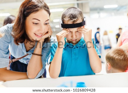 Boy with digital headset sensor connected to his brain, reading impulses, modern technology concept #1026809428