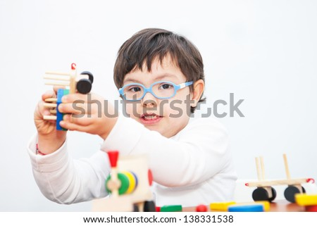 Boy with Down Syndrome playing with wooden train