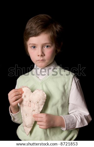 Boy with fabric heart with the word joy over a black background