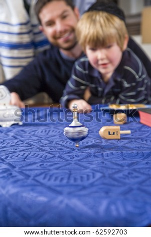 Boy with father and grandfather spinning dreidel, focus on dreidel