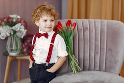 Boy with flowers. Gentelman with tulip. Mother's day. Valentines day.