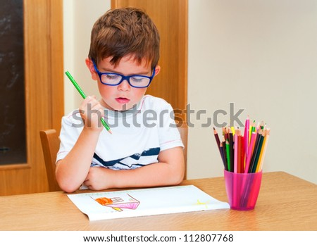 Boy with glasses drawing a house with pencils