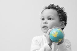 boy with globe looking up on grey background stock photo