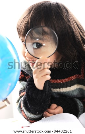 Boy with globe of earth and magnifier
