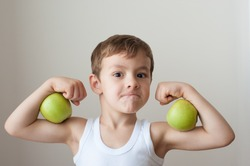 boy with green apples showing biceps