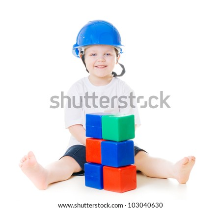 boy with hard hat playing with building blocks - stock photo