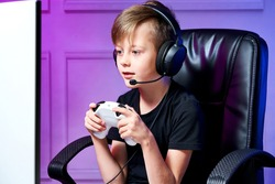 Boy with headphones plays a joystick in a computer game, looks enthusiastically at the monitor, wearing a black T-shirt, sits in a computer chair