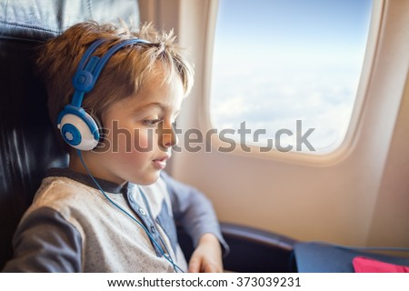 Boy with headphones watching and listening to in flight entertainment on board airplane