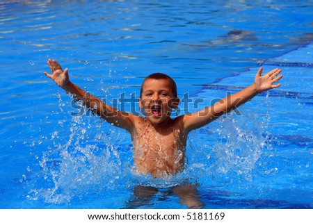 boy with his arms wide open on the pool