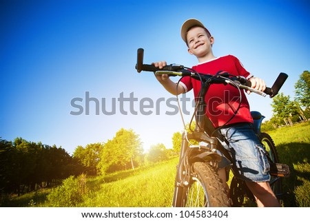 boy with his bike standing against the blue sky