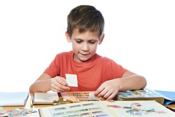 Boy with his collection of old postage stamps isolated white
