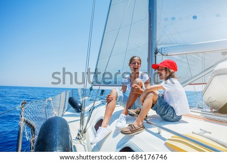 Boy with his sister on board of sailing yacht on summer cruise. Travel adventure, yachting with child on family vacation. Kid clothing in sailor style, nautical fashion. #684176746