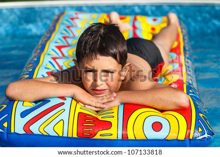 Boy with inflatable water lounger in the swimming pool