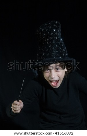 boy with magic wand on black background