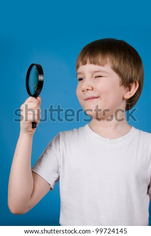 Boy with magnifying glass on a blue background
