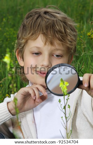 boy with magnifying glass outdoors