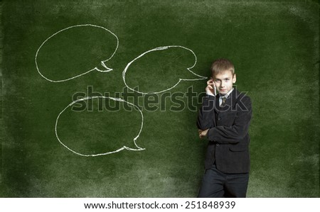Boy with mobile phone against the background of the drawing with chalk on the Blackboard