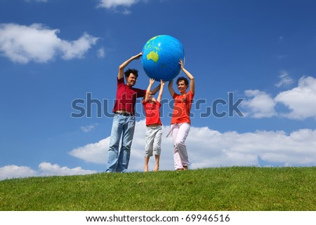 Boy with  mother and father stand on  grass and lift an inflatable globe
