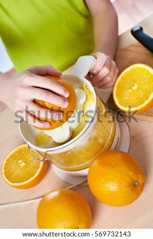 Boy with oranges makes the juice in a juicer isolated white #569732143