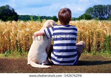 Boy with pet dog corn field in background