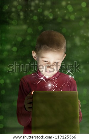 boy with present, light coming out of the box