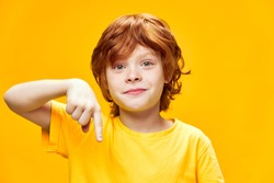 Boy with red hair front view yellow isolated background with a happy and excited expression